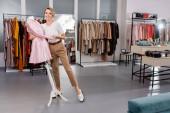 Veselý blondýny prodejce objímající růžový kabát na figuríně v showroomu