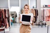 Veselý prodejce držící digitální tablet s prázdnou obrazovkou na rozmazaném popředí v showroomu