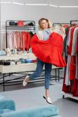 Happy zákazník skákání s šaty na ramínku v showroom