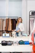 Blondýny zákazník chůze v blízkosti oblečení a příslušenství v showroom