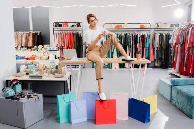 Blonde seller using smartphone near shopping bags in showroom stock vector
