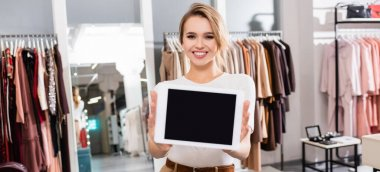 Seller smiling at camera while holding digital tablet with blank screen in showroom, banner stock vector