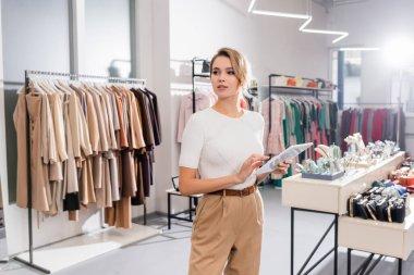 Genç satıcı galeride kıyafetlerle dikilirken dijital tablet kullanıyor.