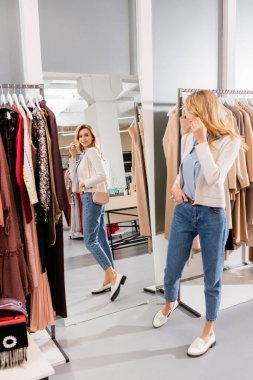 Smiling woman with handbag looking at mirror in showroom