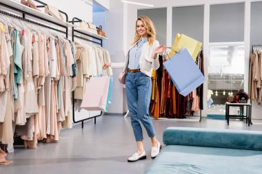 Cheerful customer with colorful shopping bags standing in showroom