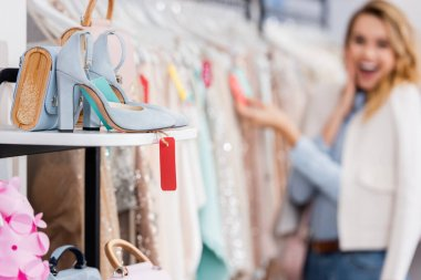 Shoes with price tag and handbag near woman on blurred background in showroom
