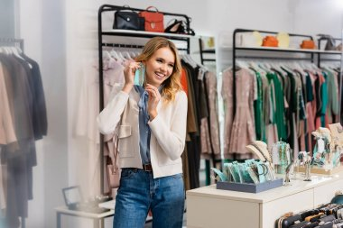 Cheerful woman holding earrings in showroom stock vector