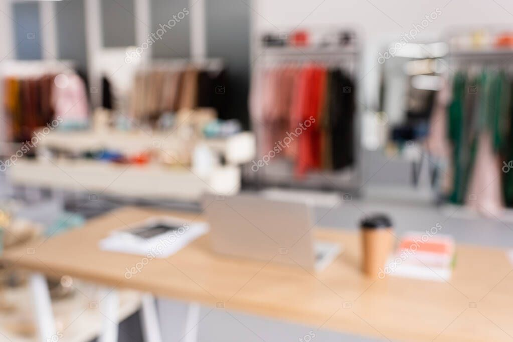 Blurred background of laptop in showroom with clothes stock vector