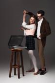 stilvolles, altmodisches Paar, das in der Nähe eines Plattenspielers auf dunkelgrauem Hintergrund tanzt