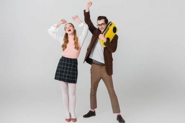 cheerful man holding vintage boombox while dancing with excited woman on grey