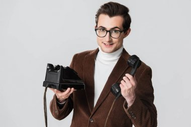 Young man in brown blazer smiling at camera while holding vintage phone isolated on grey stock vector