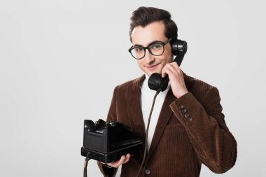 Smiling man in eyeglasses and velvet blazer talking on vintage phone isolated on grey stock vector