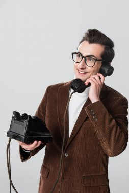 Happy man in velvet blazer looking away while calling on vintage phone isolated on grey stock vector