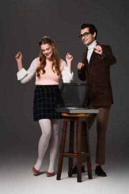 cheerful, old fashioned couple dancing near record player on dark grey background