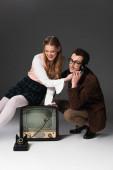 mosolygós férfi beszél telefonon közelében vidám nő ül vintage tv szürke háttér