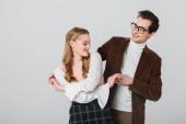 altmodische Mann mit Brille tanzen mit junger Freundin isoliert auf grau