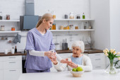 young nurse giving glass of water and medication to senior woman in kitchen