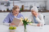 usmívající se zdravotní sestra čtení knihy šťastné starší ženy v blízkosti čerstvých jablek a tulipánů v kuchyni