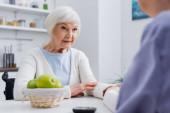 Senior-Diabetikerin schaut Sozialarbeiterin nahe verschwommenem Glukometer an