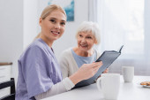 happy social worker looking at camera while holding photo album near aged woman