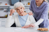 starší žena ukazuje kus skládačky, zatímco zdravotní sestra dotýká její rameno