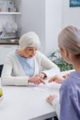 aged woman pointing with finger while playing jigsaw puzzle with social worker