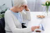 seniorka, trpí ztrátou paměti, dívá se na kalendář doma