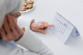 cropped view of elderly woman, suffering from memory loss, pointing at calendar, blurred foreground