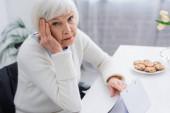 stárnoucí žena, nemocná na demenci, dotýkající se hlavy při pohledu do kamery poblíž kalendáře