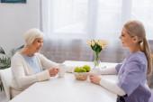radostná starší žena a mladý sociální pracovník mluví v kuchyni v blízkosti čaje a čerstvá jablka