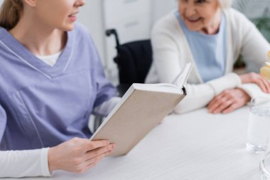 Cropped view of young nurse reading book to elderly woman, blurred background stock vector