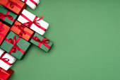Photo top view of multicolored gift boxes with red ribbons on green background with copy space