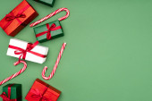 top view of colorful gift boxes and candy canes on green background with copy space