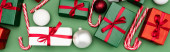 Photo panoramic concept of colorful gift boxes, candy canes and christmas balls on green background, top view