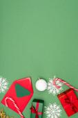 horní pohled na dárkové krabice, obálka s kartou, vánoční ples, candy canes a dekorativní sněhové vločky na zeleném pozadí s kopírovacím prostorem