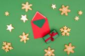 top view piros boríték kártyával ajándékdoboz közelében, sült hópelyhek és csillagok zöld
