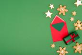 top view piros boríték kártyával közel sült hópelyhek és a csillagok zöld háttér másolási hely
