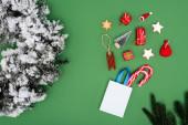 felső kilátás bevásárló táska cukornád közelében karácsonyi baubles és fenyő koszorú dekoratív hó zöld háttér