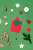 top view piros boríték kártyával közel karácsonyi baubles, sült csillagok és cukornád zöld