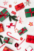 top view of gift boxes, candy canes, star-shaped cookies, fir branches and decorative snowflakes on white background