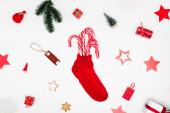 červená vánoční punčocha s cukrovinkami v blízkosti cookies a slavnostní ozdoby na bílém pozadí