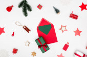 top view of red envelope with card near christmas baubles on white background