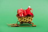 červené dárkové krabice a Santa klobouk v proutěném koši na ozdobných saních na zeleném pozadí
