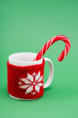 Photo candy cane in cup with knitted cup holder with snowflake on green background