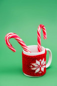 Photo two candy canes in cup with knitted cup holder with snowflake on green background