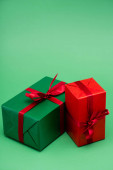 two colorful gift boxes with red ribbons and bows on green background