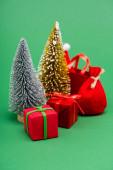 stříbrné a zlaté ozdobné vánoční stromky v blízkosti dárkových krabic, sáčku a nákupní tašky se Santou na zeleném