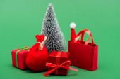 stříbrný ozdobný vánoční stromek v blízkosti dárkových krabic, pytel a nákupní taška se Santou klobouk na zelené