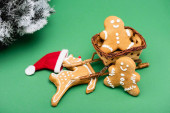 gingerbread men and deer in santa hat near decorative sleigh, and fir branch with snow on green