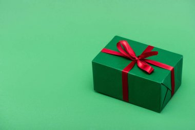 Colorful gift box with red ribbon and bow on green background with copy space stock vector